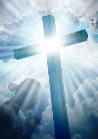 Silhouette of a women praying under the cross Stock Photo