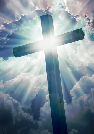 Christian cross on a blue sky with clouds and sunlight background