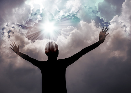 Silhouette of a woman praising to God