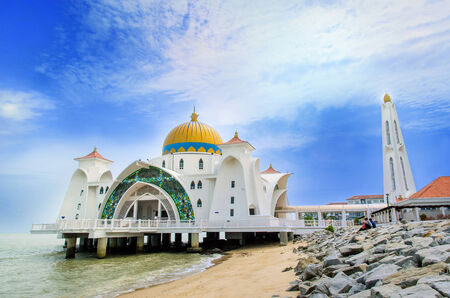 straits: Malacca,Malaysia - June 15, 2014   People can seen exploring around the Malacca Straits Mosque in Malaysia