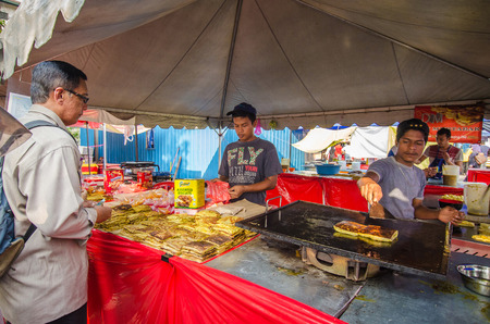 break fast: Kuala Lumpur,Malaysia - July 23, 2014 The food seller preparing Murtabak fried for their customers during Ramadan bazaar in Kuala Lumpur It is established for muslim to break fast during the holy month of Ramadan  Editorial