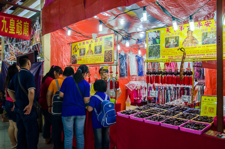 workship: Selangor,Malaysia - September 26, 2014 : During the The Nine Emperor Gods Festival,there are some stalls around the temple selling religious prayer ornaments,paraphernalia and other accessories.People can seen buying stuff in front of the stall. Editorial