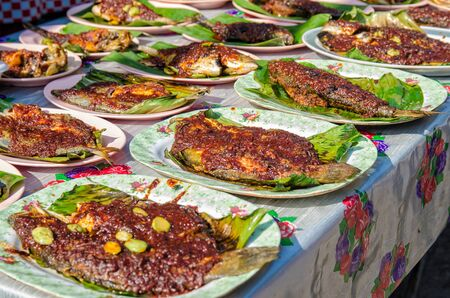 Grilled fish with spicy sauce on plate selling in Ramadan Bazaar Kuala Lumpur during the holy month of Ramadan. Archivio Fotografico