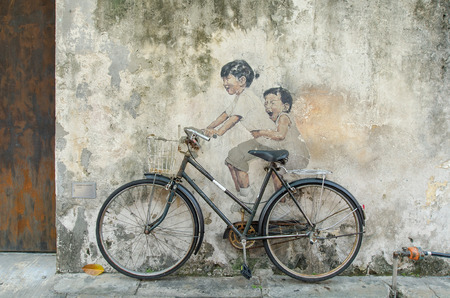 georgetown: Georgetown,Penang - July 17,2015 :  Little Children on a Bicycle painted by Ernest Zacharevic in street art Georgetown, Penang
