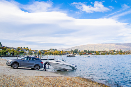 Wanaka,New Zealand - April 29,2016 : A man using his car to towing the boat from the lakeside.