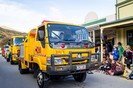 antique fire truck: Arrowtown, New Zealand - April 23,2016 : There is parade event during the Arrowtown Autumn Festival on Buckingham Street, people can seen watching and enjoying the parade. Editorial
