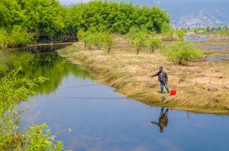 city park boat house: Lijiang,China - April 14,2017 : Lijiang Lashi Lake Wetlands is a national natural scenic spot near the city of Lijiang,China. A person can seen fishing on the lake. Editorial