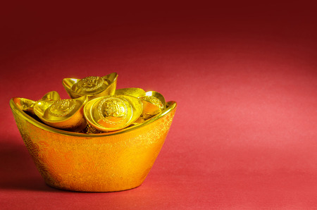 Chinese New Year gold ingots decorations on red background. (English translation for foreign text means blessing).