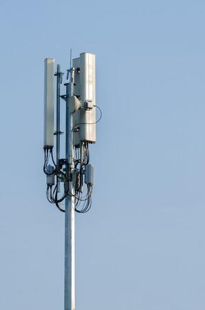 Telecommunicatie toren antenne op blauwe hemelachtergrond.