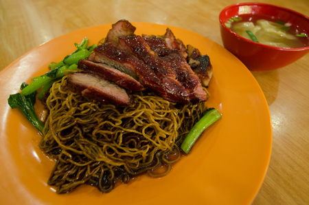 Close-up view of the wantan mee served with soy sauce,roast pork and vegetable. It is a Cantonese Chinese cuisine. Stock Photo