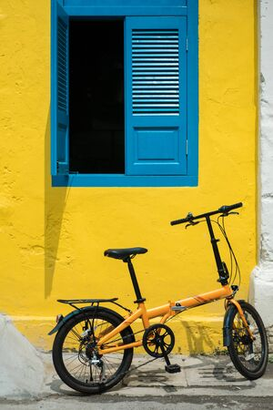 Bicycle parked in front of the shop house with yellow wall and antique blue window
