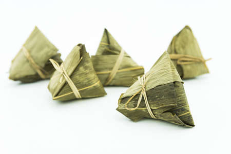 Closeup view of the zongzi (sticky rice dumplings), it is a traditional Chinese rice dish made of glutinous rice stuffed with different fillings and wrapped in reed leaves.