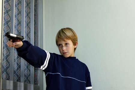 delincuencia: Delincuencia juvenil. Golpeado ni�o apuntando a la puerta de una casa con una pistola