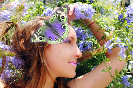 Beautiful woman in nature among flowers and butterflies. Stock Photo