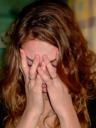 Woman crying and holding his face in his hands photo