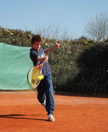 child in tennis practice on clay court