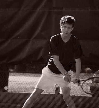 Teenager playing tennis hitting the ball photo