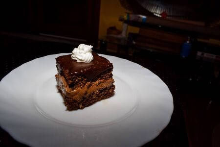 Chocolate cake with a touch of whipped cream on top