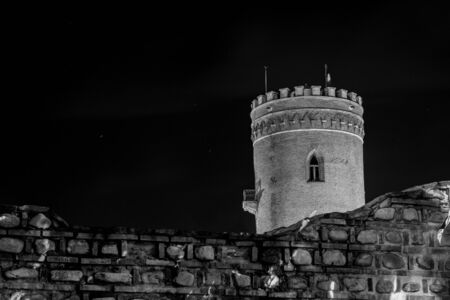 Black and white composition of a medieval ruin of a watch tower at night with stone wall in the foreground