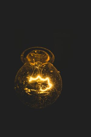 Closeup of a lit up light bulb with glowing filament on a black background