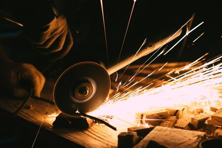 Man cutting a piece of metal with an angle grinder with sparks jumping out of it 版權商用圖片