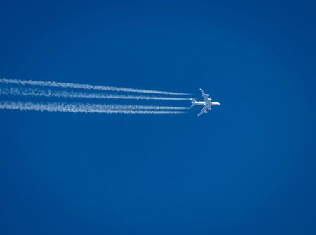 Flying airplane leaving contrails behind it