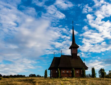 Old wooden church with thuja trees in front on a cloudy blue sky in Maramures