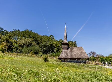 Old wooden church in a green meadow near a cemetery and forest in a rural landscape in Maramures