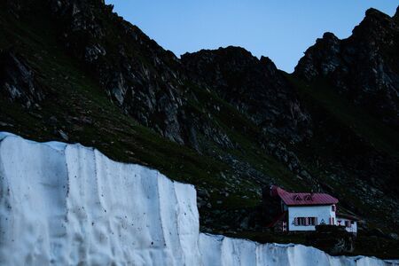 Ice wall near a search and rescue house in the mountains