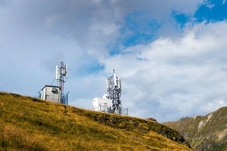 Cell towers on a mountain hill with white clouds on a blue sky above