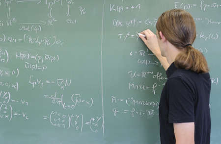 formulae: student teacher writing math on chalkboard Stock Photo
