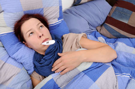 body temperature: ill woman with fever thermometer in bed