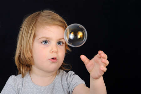 Marvelling kid girl and soap bubble Stock Photo