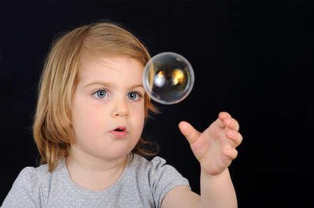 Marvelling kid girl and soap bubble Reklamní fotografie