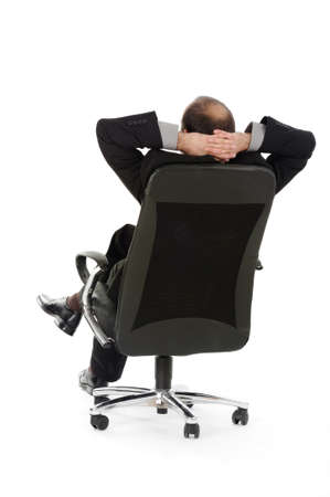 lean back: Back view of businessman in office swivel chair Stock Photo