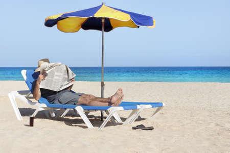 怠惰なビーチで男を読んで新聞をリラックス 写真素材