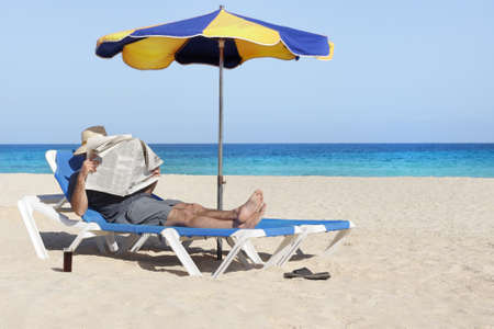 perezoso: Lazy peri�dico relajante lectura del hombre en la playa