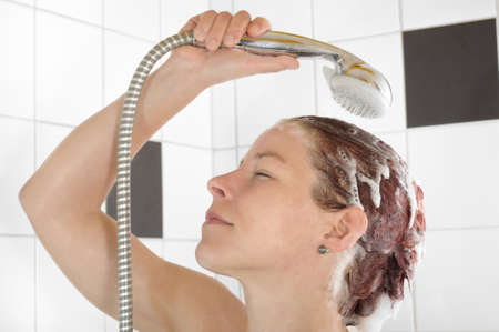 Woman rinsing her hair under the shower photo