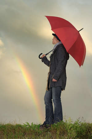 Woman with umbrella  grass field with rainbow