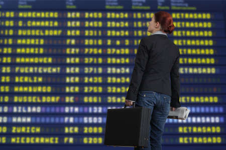 cancellation: Woman checking the airport flight timetable