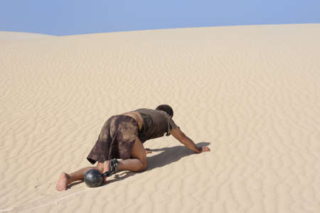 toiling: Man with ball and chain crawling through desert Stock Photo