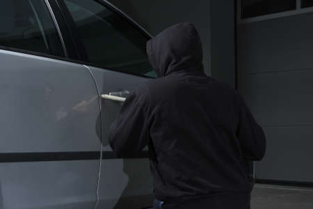 thievery: Thief trying to break a car Stock Photo