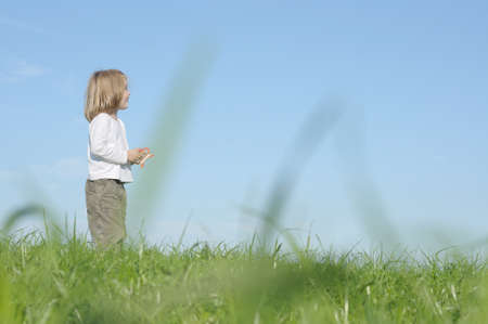 Girl playing outdoors in meadow Stock Photo