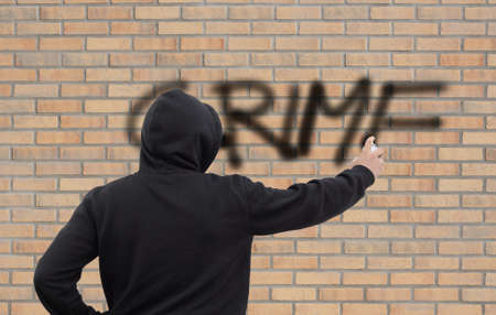 Hooded person spraying crime on a wall Stock Photo
