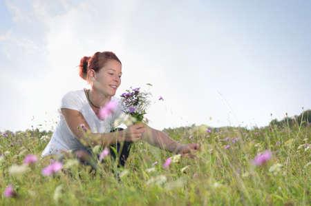 Vrouw het plukken bos bloemen in de weide