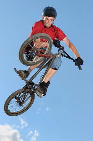 Professional BMX biker making a tabletop on dirt jump Stock Photo