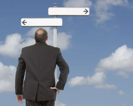 Businessman at decision signpost Stock Photo