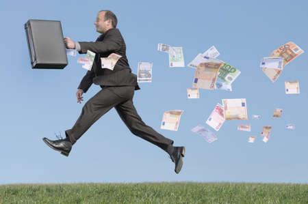 紙幣のブリーフケースを使って男を実行しています。 写真素材