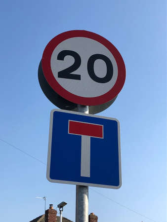 Street signs indicating a 20 mph miles per hour speed limit and a T junction