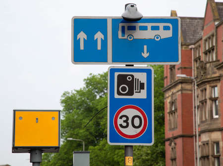 Street signs indicating the presence of bus lanes speed limits and speed cameras Preston Lancashire June 2018